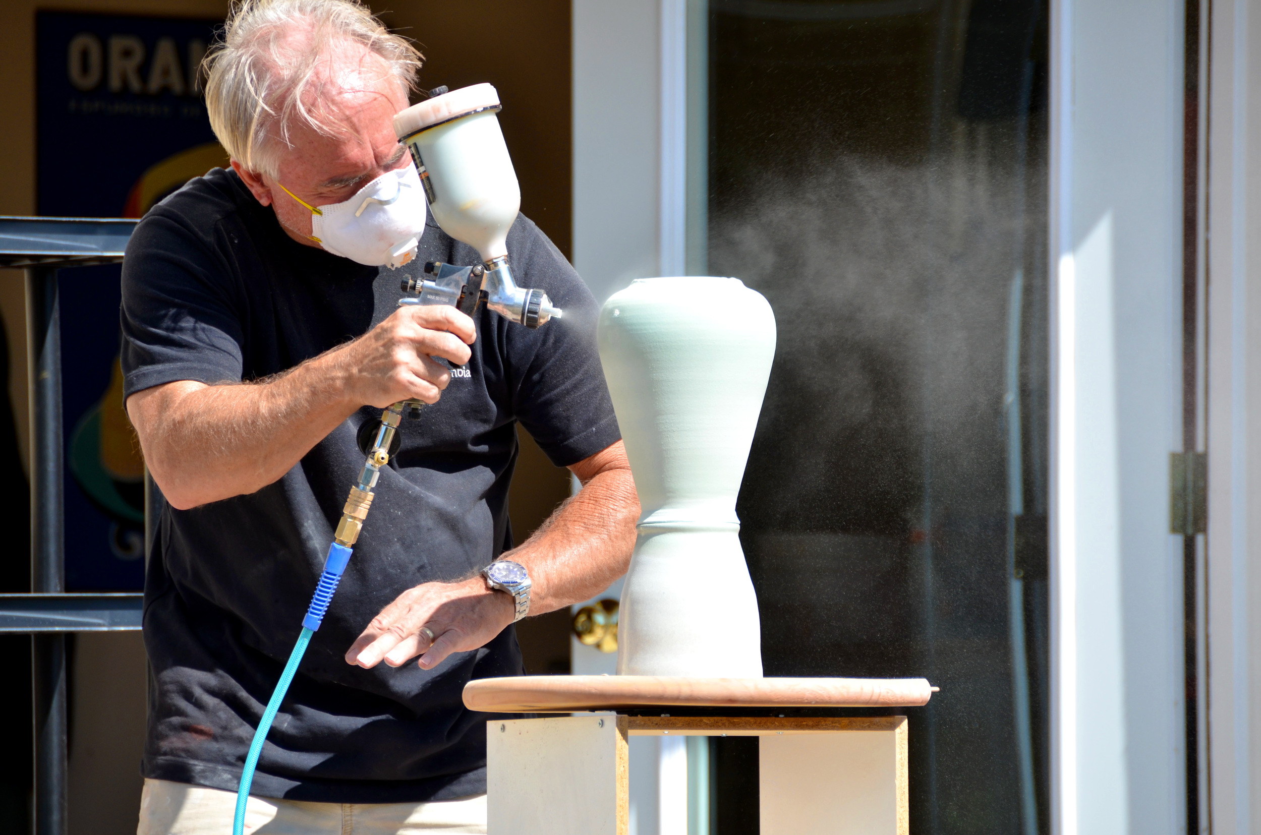 David Caldwell hand glazing porcelain pieces in their Park City studio | Caldwell Pottery