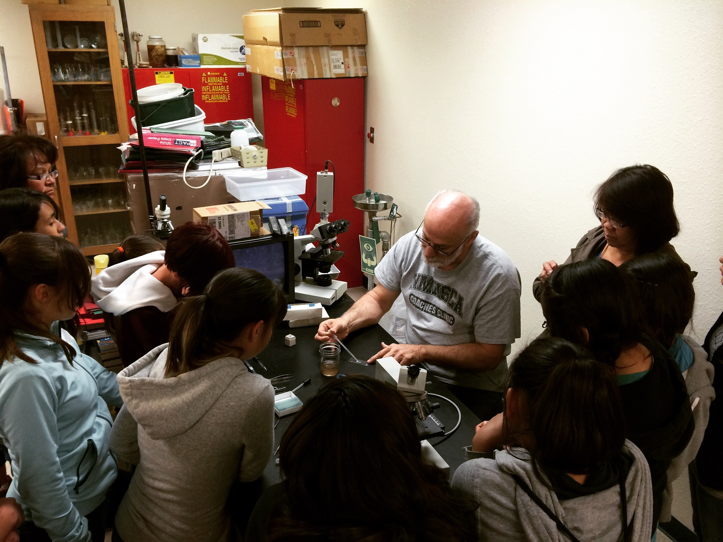Mr. Gary Hoodless teaches students how to prepare a microscope slide