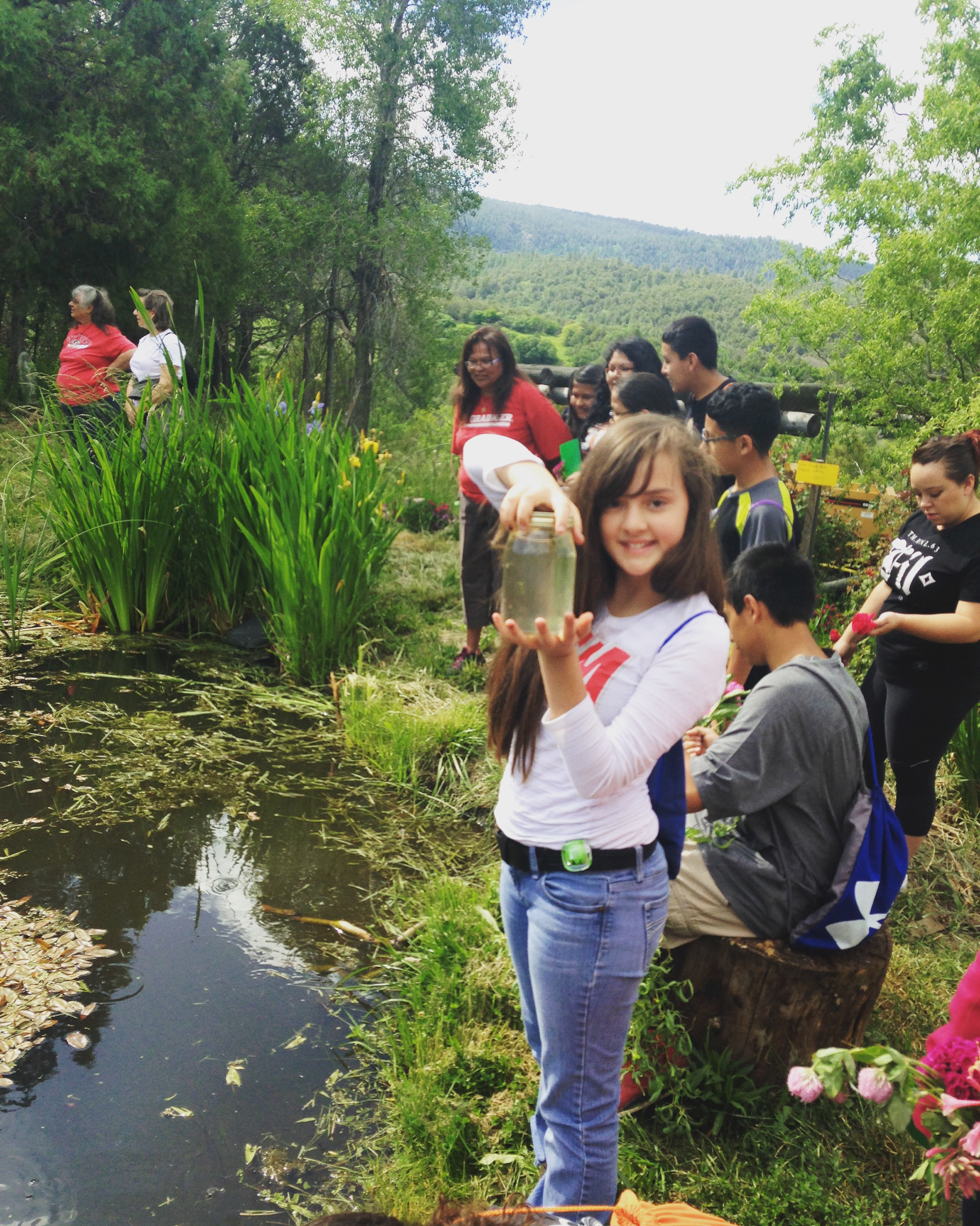 Students gather pond water to create microscope slides in the lab