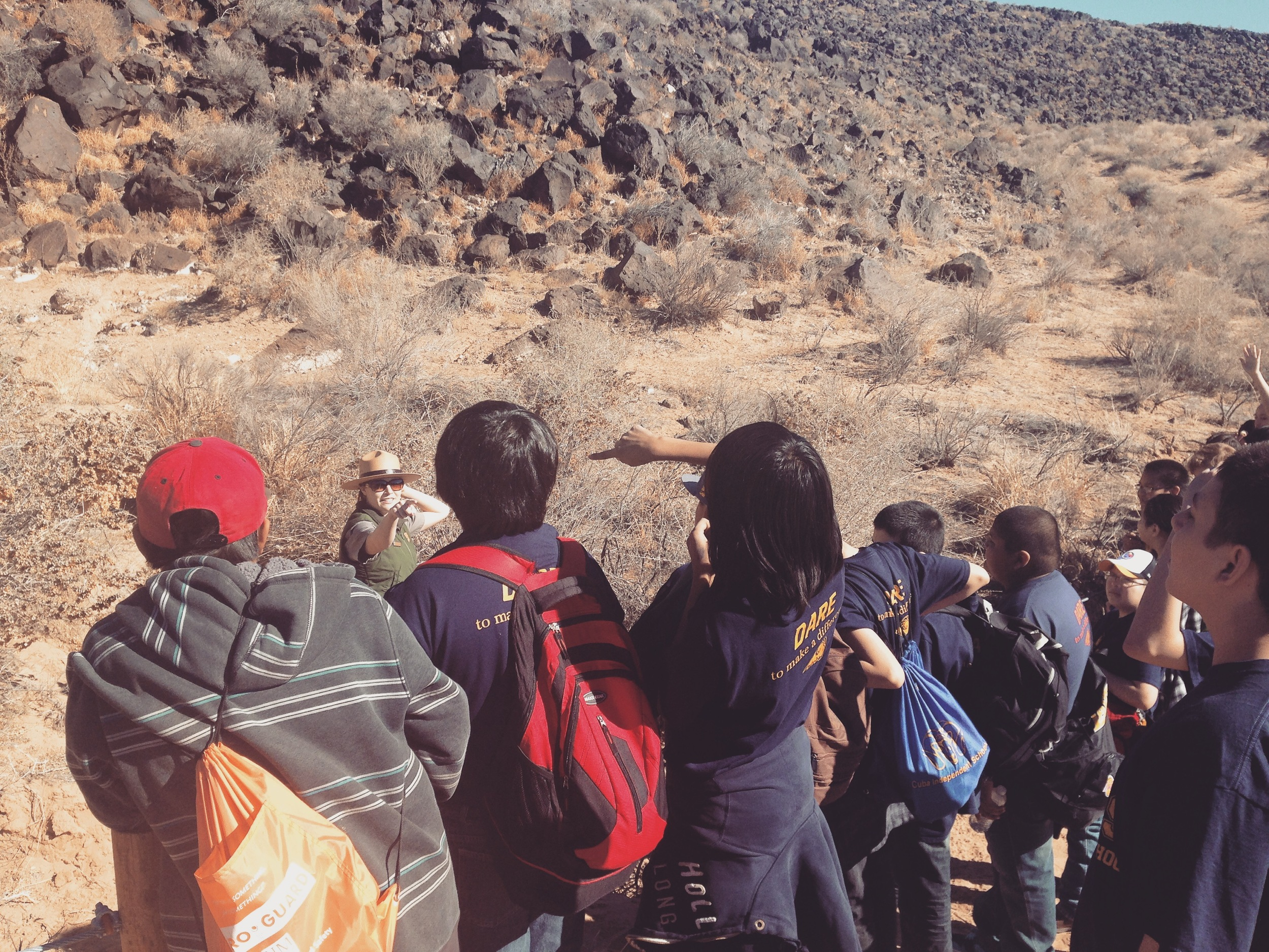 Students point out petroglyphs to one another at the Petroglyph National Monument