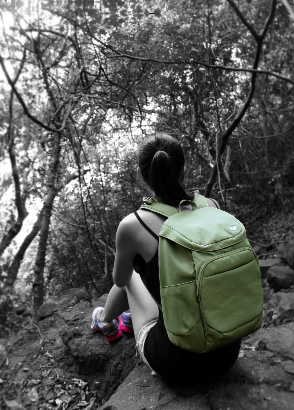 woman-sitting-down-hiking-with-green-pacsafe-backpack