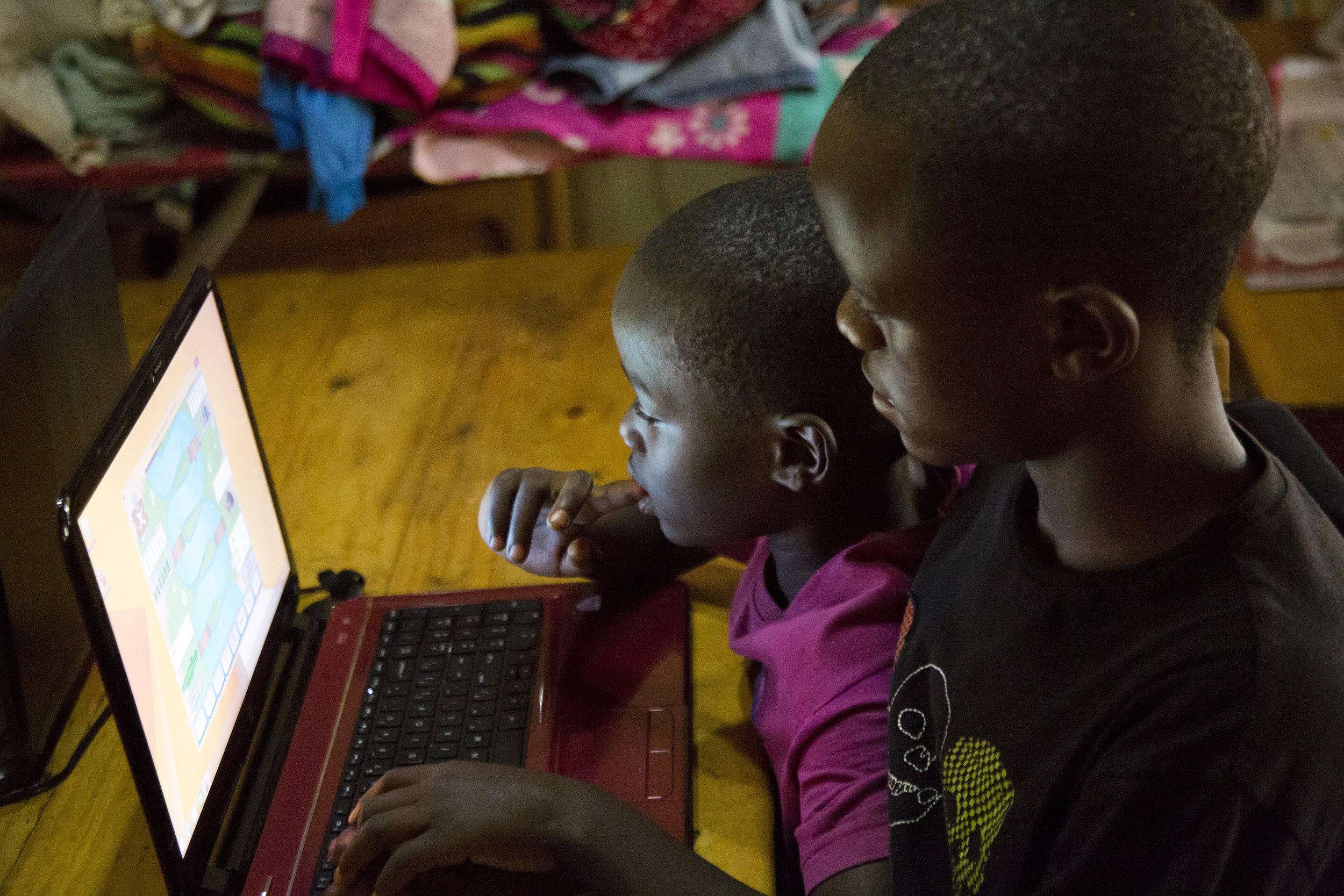 Janvier helping Manzi out with a typing program