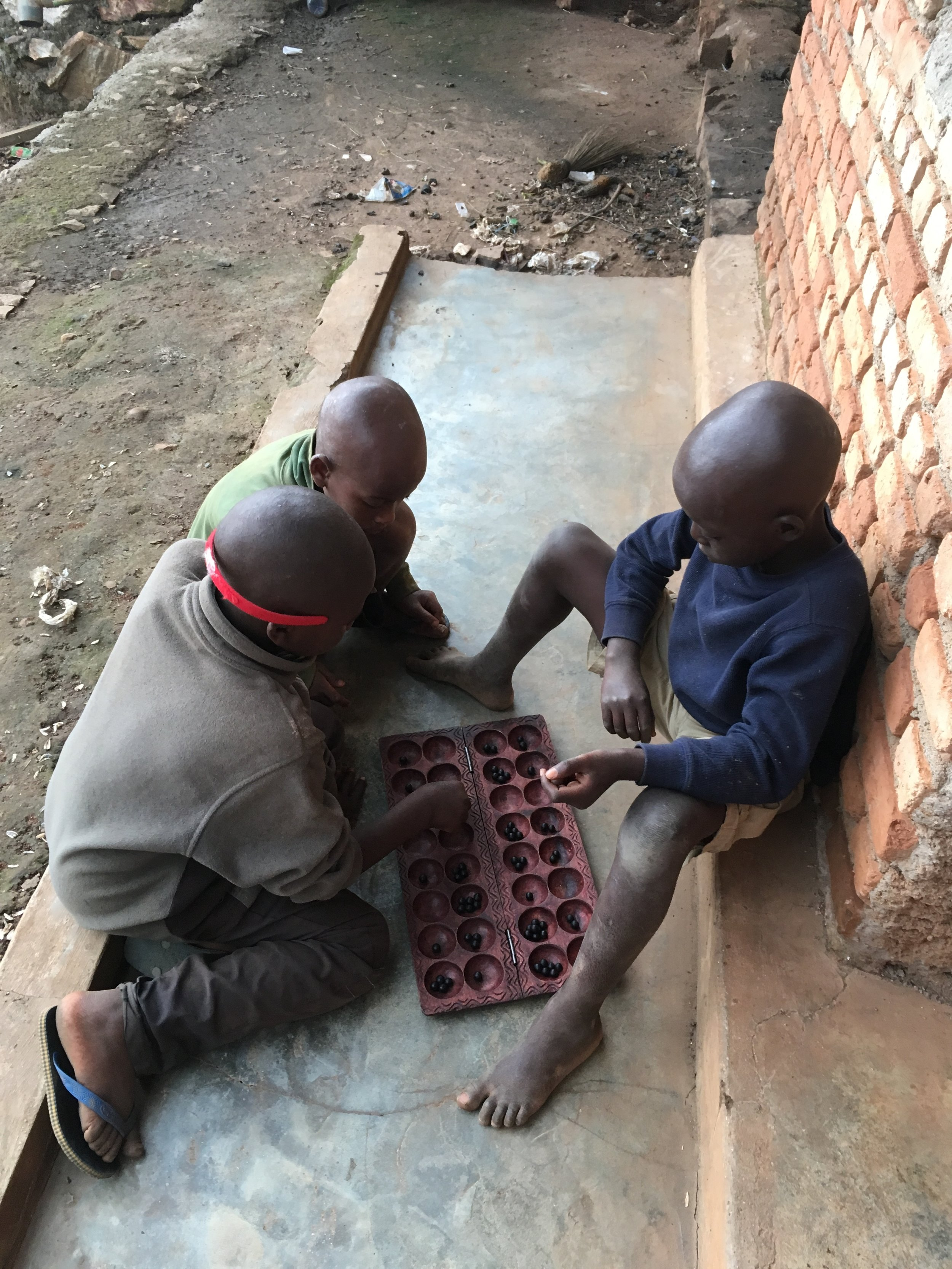 The little ones learning a traditional game called Igisoro. It has similarities to Mancala. They picked it up pretty quick.