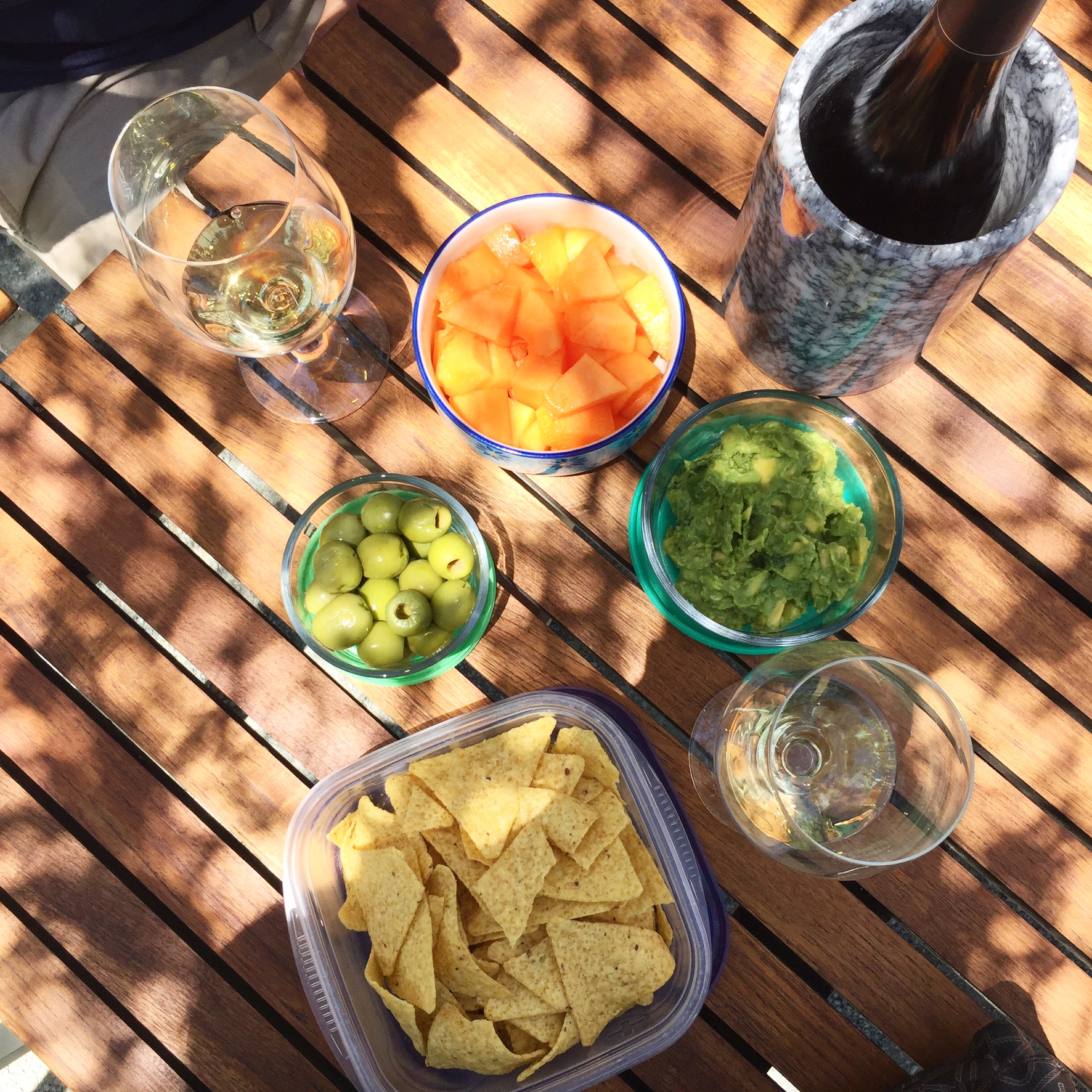 Picnic while wine tasting: tortillas chips, guacamole, green olives, cantaloupe.