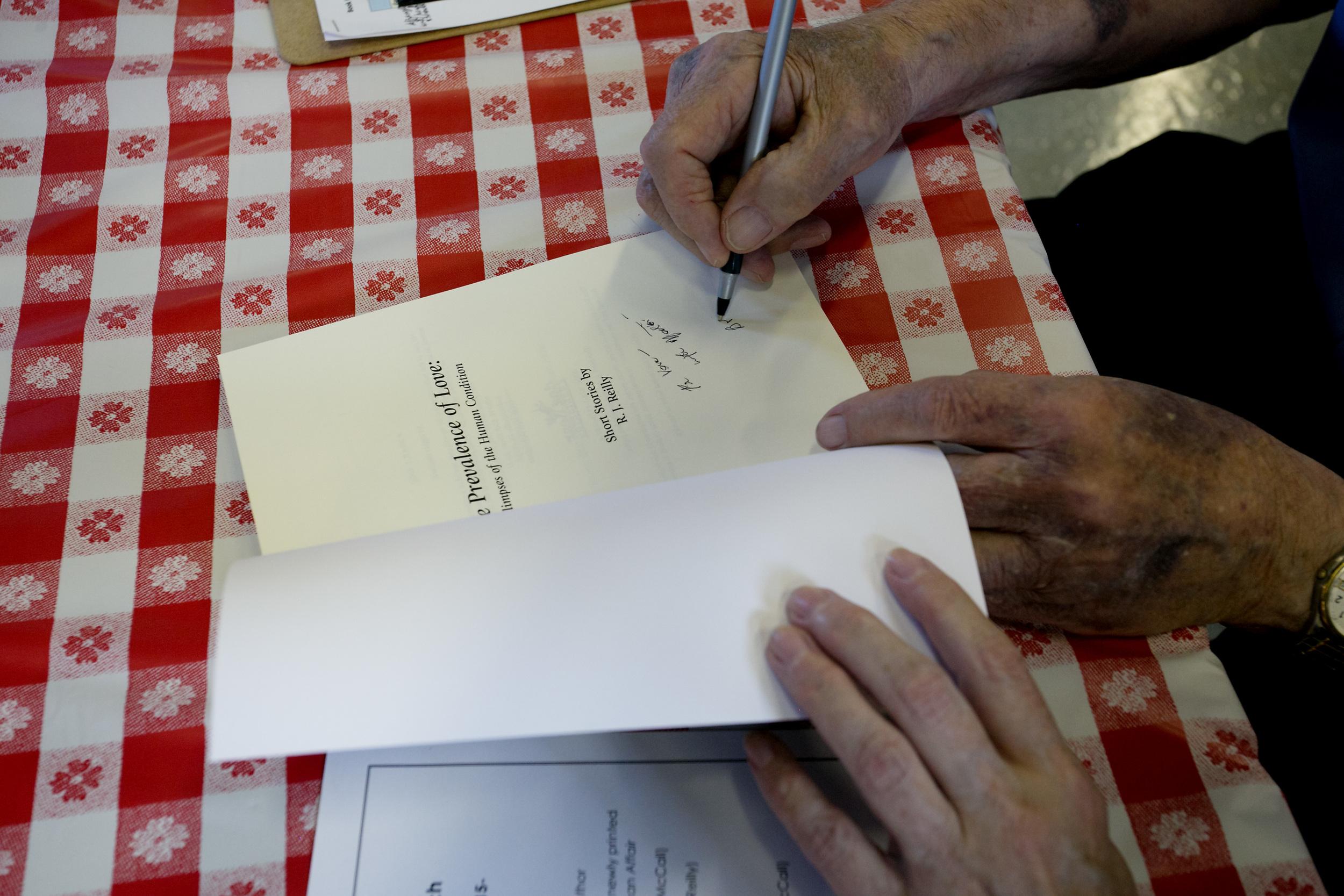 Bob signs a book.jpg