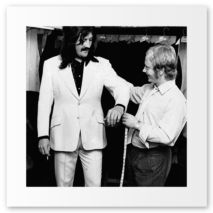 "Known to many as the greatest ever rock drummer. Known to my Dad as John: friend & capable drinking partner. John Bonham pictured here in the early 70's being measured up for one of his many white suits. A brilliant customer, as come Monday morning, jacket in hand, displaying the excess of the weekend, he'd announce ""Pete, I need a new one..."""