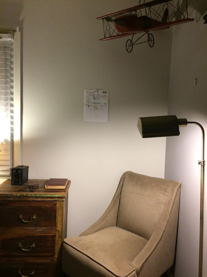 CORRECT - paper taped to the wall, head on shot, furniture visible.