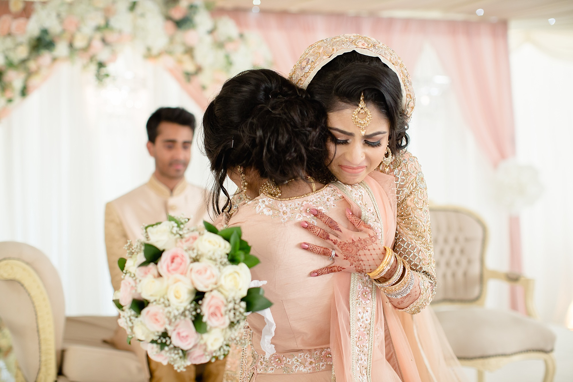 Bride and sister hug at Hilton Hall Wolverhampton