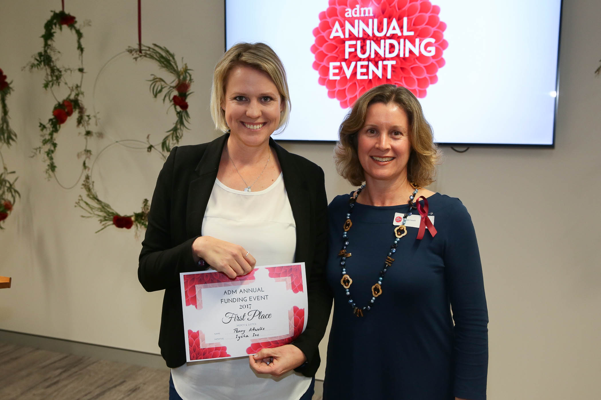 Penny Attwells (left) accepts her award from Margo Leach, ADM's Director of Mercy & Justice Ministries.