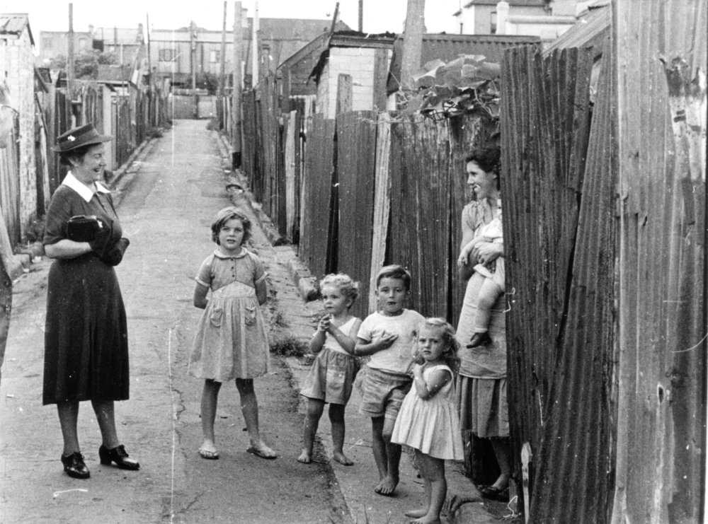 Mary Andrews visiting a family in Erskineville