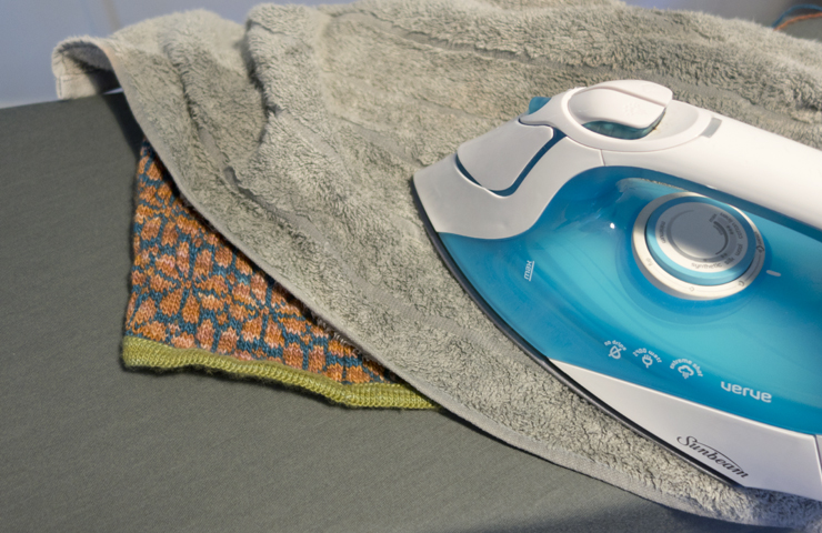 To block a small area: Wet a towel. Place that towel over work. Press with an iron for a few seconds. Lightly stretch work. Repeat.