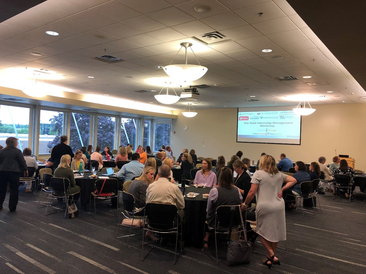 Workshop participants networking in the Cascade Room at St. Cloud State University at the beginning of the event