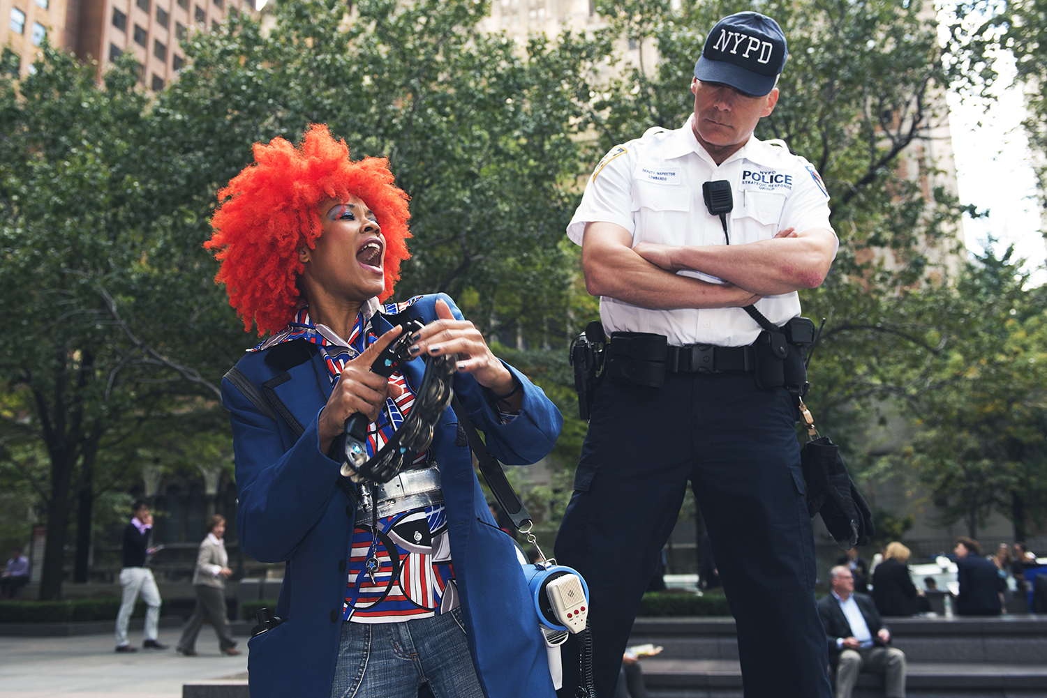 An NYPD officer keep watching over an anti-abuse of climate  demonstrator on Park Avenue, Manhattan. 2015   ©    Go Nakamura     photography