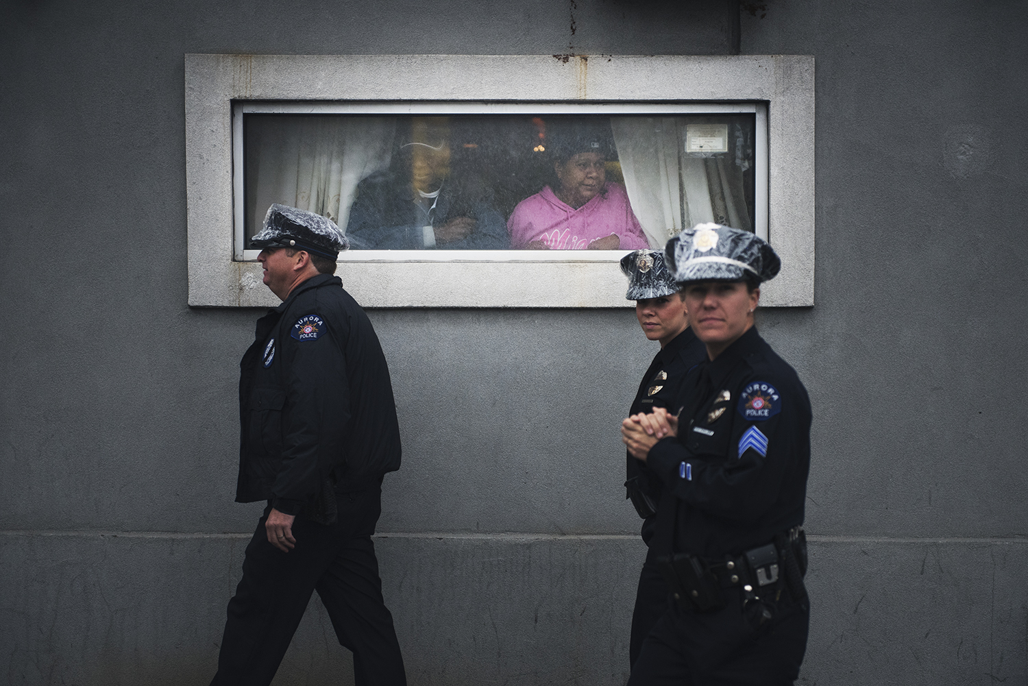 a couple of people look out a window as a group of police officers walk by, heading to The Greater Allen AME Cathedral in Jamaica, Queens for slain NYPD officer Hold's funeral. Queens, NY. 2015   ©    Go Nakamura     photography