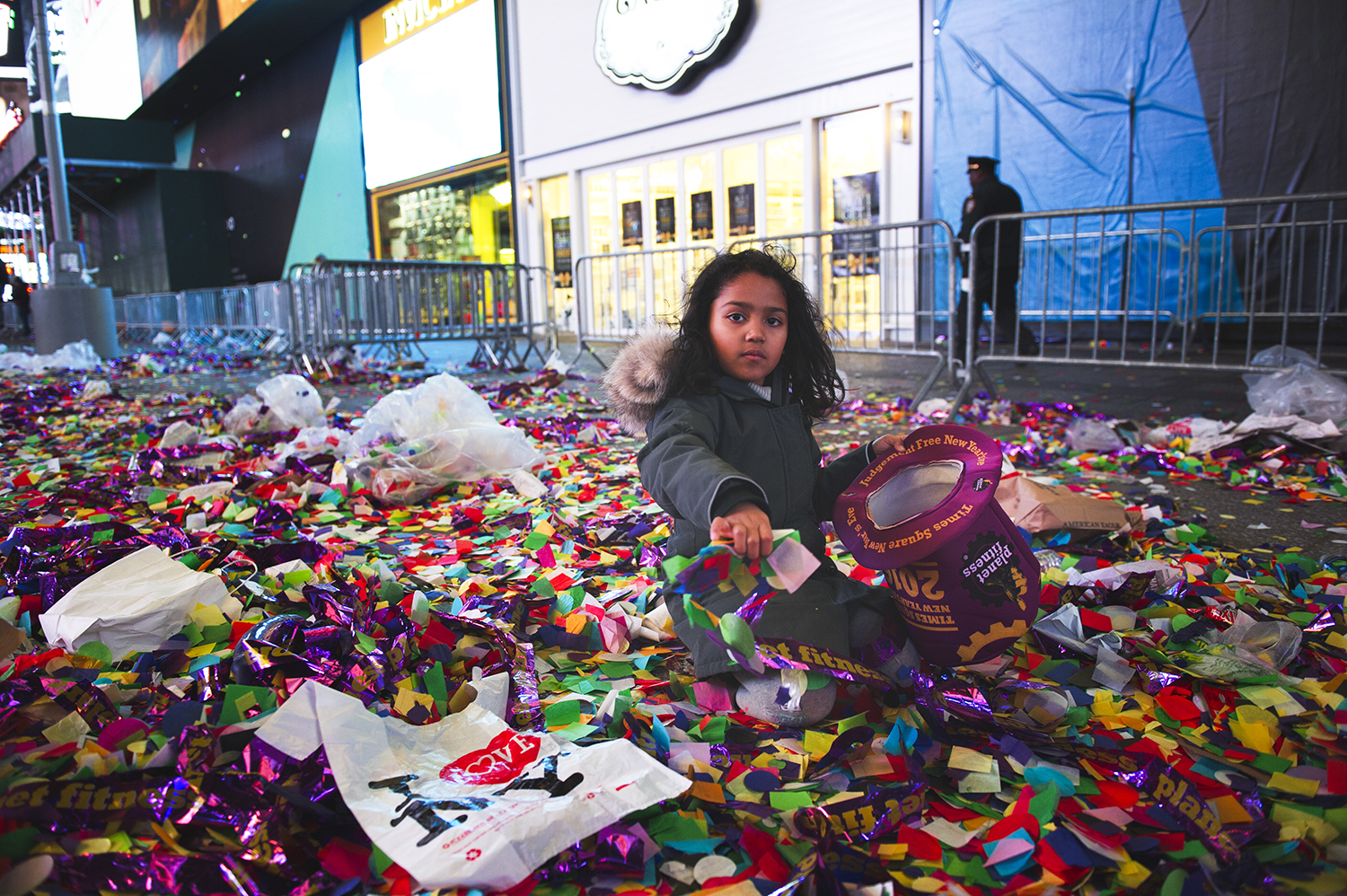 a girl plays with confetti what was used for New Year Countdown event in Times Sq, NY. 2016  ©    Go Nakamura     photography