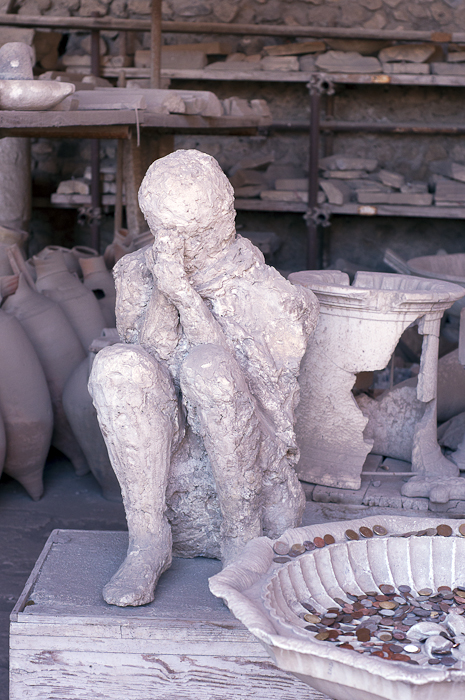 A man squats to take refuge from Vesuvius