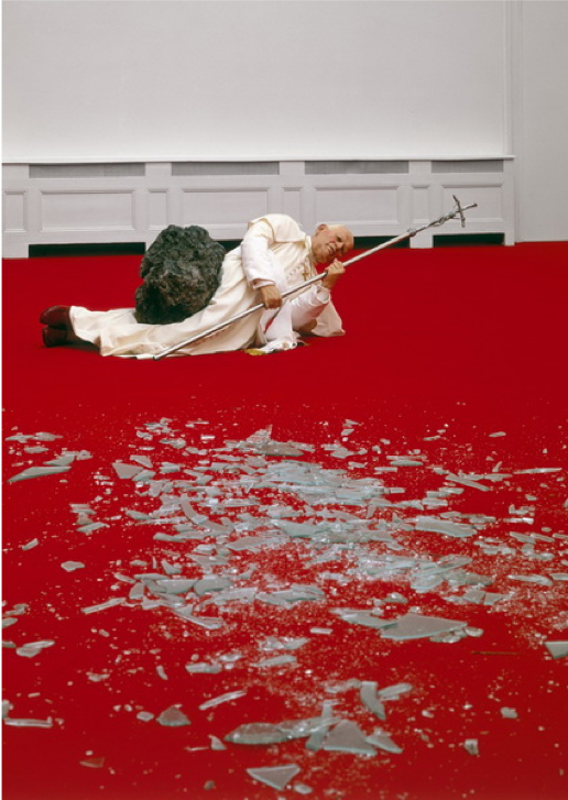 Maurizio Cattelan,  The Ninth Hour , 1999, wax, clothing, polyester resin with metallic powder, volcanic rock, carpet, glass, Private Collection.  https://www.wikiart.org/en/maurizio-cattelan/the-ninth-hour-1999
