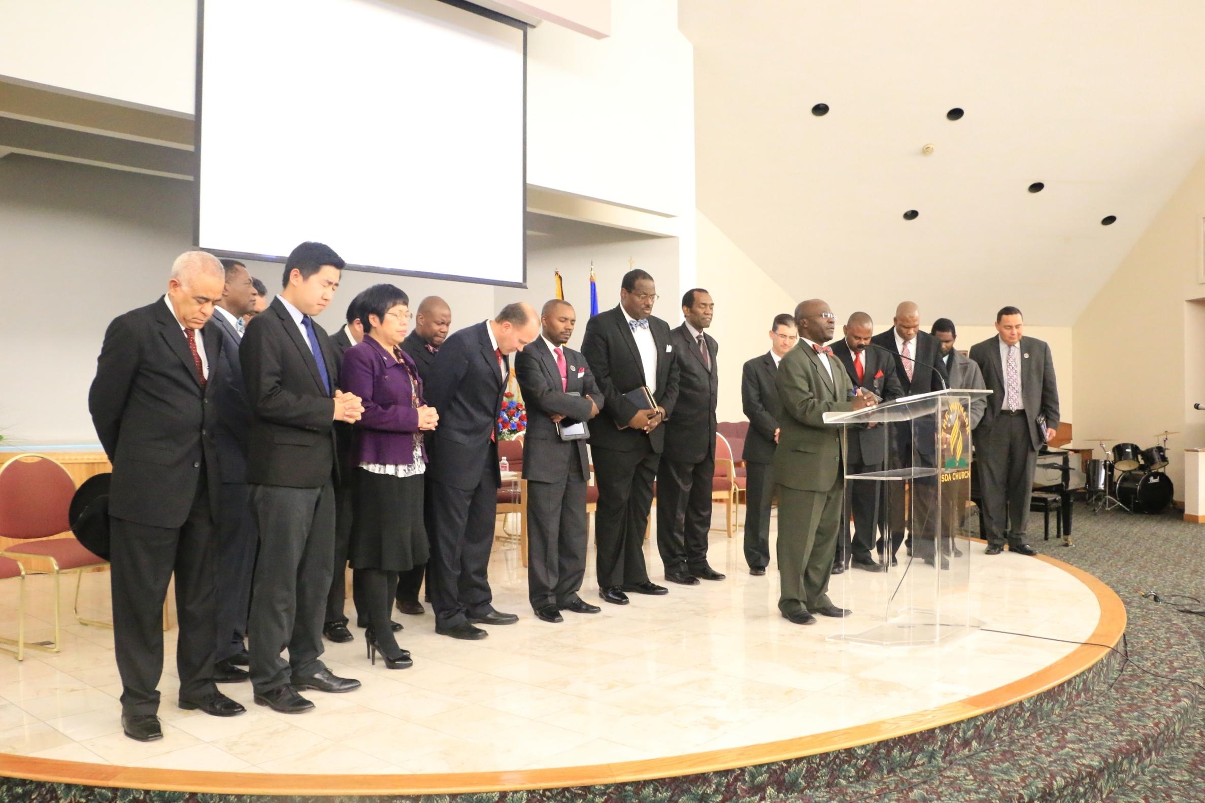 Elder John Amoah offers a dedicatory prayer, with Boston-area pastors behind him.