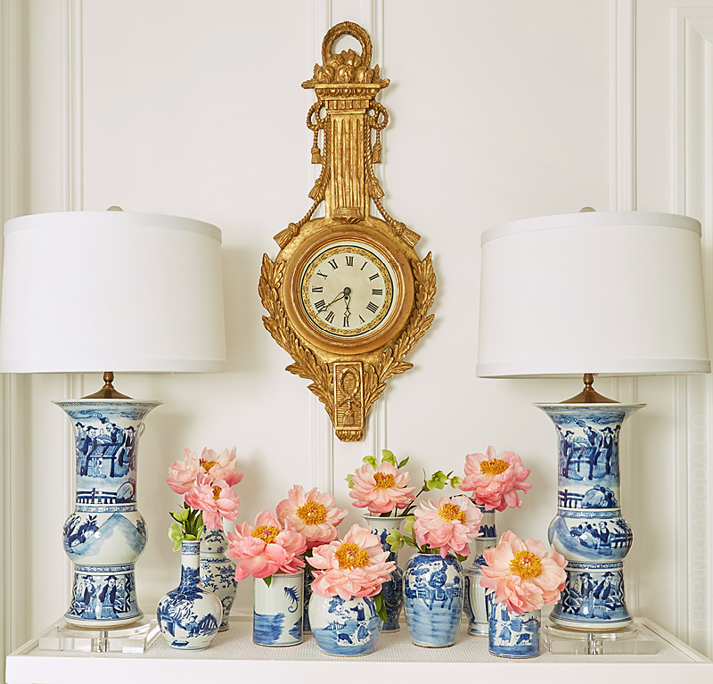 pink peonies in small blue and white vases on an oomph console table with Farrow and Ball's All White paint and Metrie mounlding