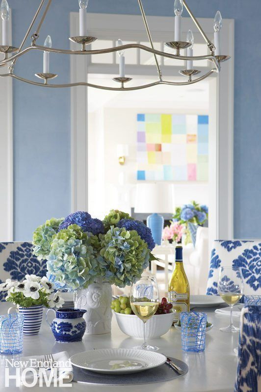 Tabletop with Wedgewood's Nantucket dinnerware, blue hydrangeas, blue and white fabric and accessories, and a fun, colorful painting by Ben Georgia in this lovely Nantucket getaway designed by Lynn Morgan