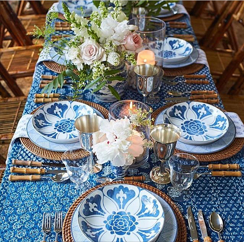 Blue and white tabletop with lots of rattan, bamboo, peonies and roses.