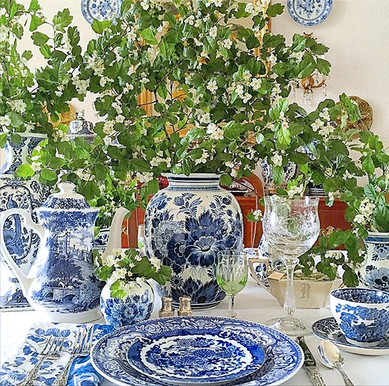 Blue and white tabletop with a profusion of flowers and foliage.