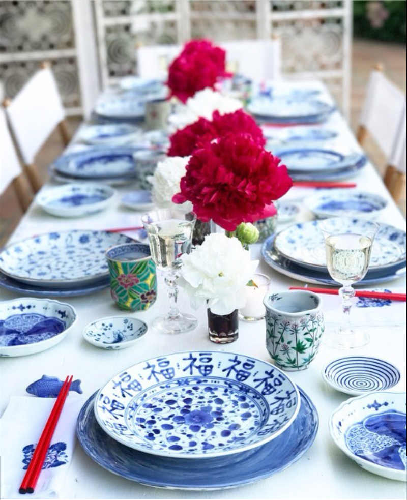 A blue and white Chinese inspired tabletop with red and white peonies.