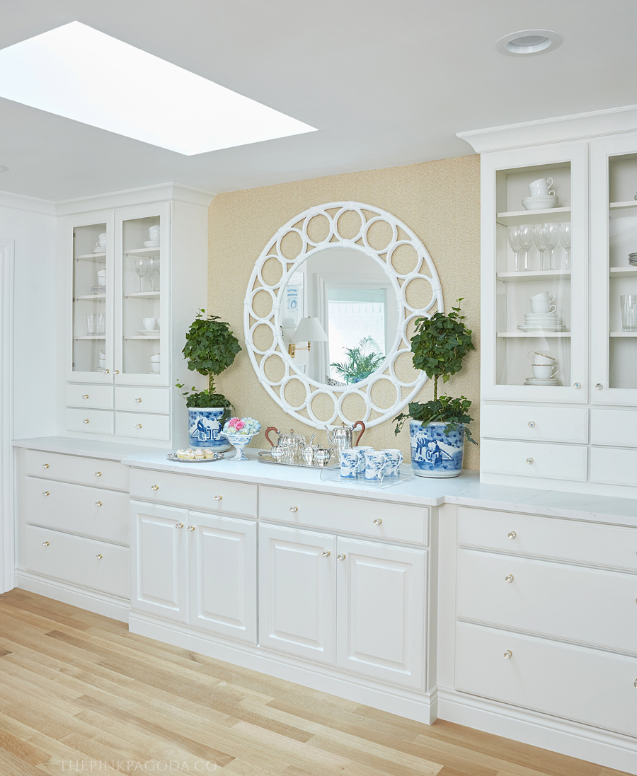 Built for The Pink Pagoda's One Room Challenge™ breakfast room area, this cabinetry serves as storage, display, and a perfect buffet option. To fill the large open space of the buffet, she used large blue and white planters with topiaries, a large scale, fun, round mirror, a Juliska compote and mugs, and a silver service.