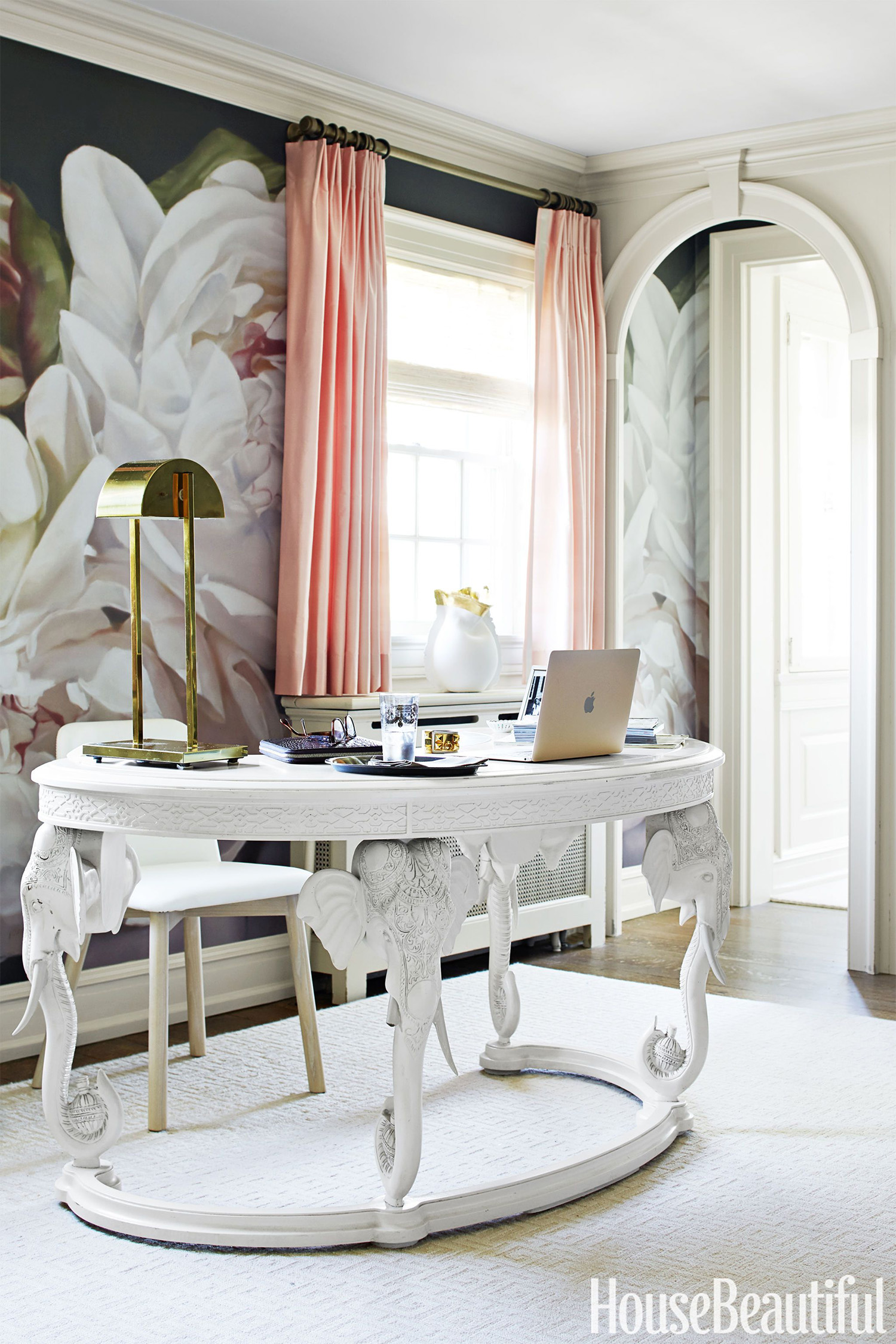 The master bedroom walls are accented by a custom mural wallcovering of massive peonies by artist Thomas Darnell for Area Environments. The vintage elephant desk is from Again & Again in Dallas, TX.