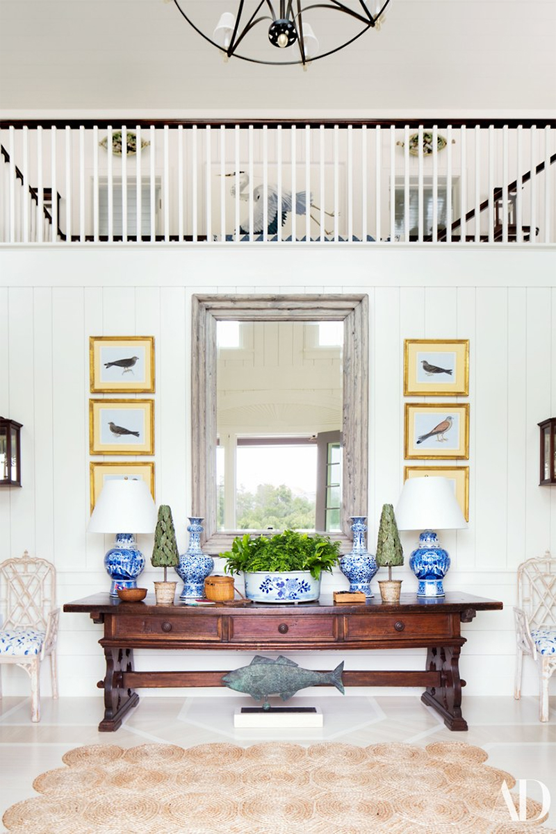 Bird prints hang above an antique console table topped with a vista of blue and white.