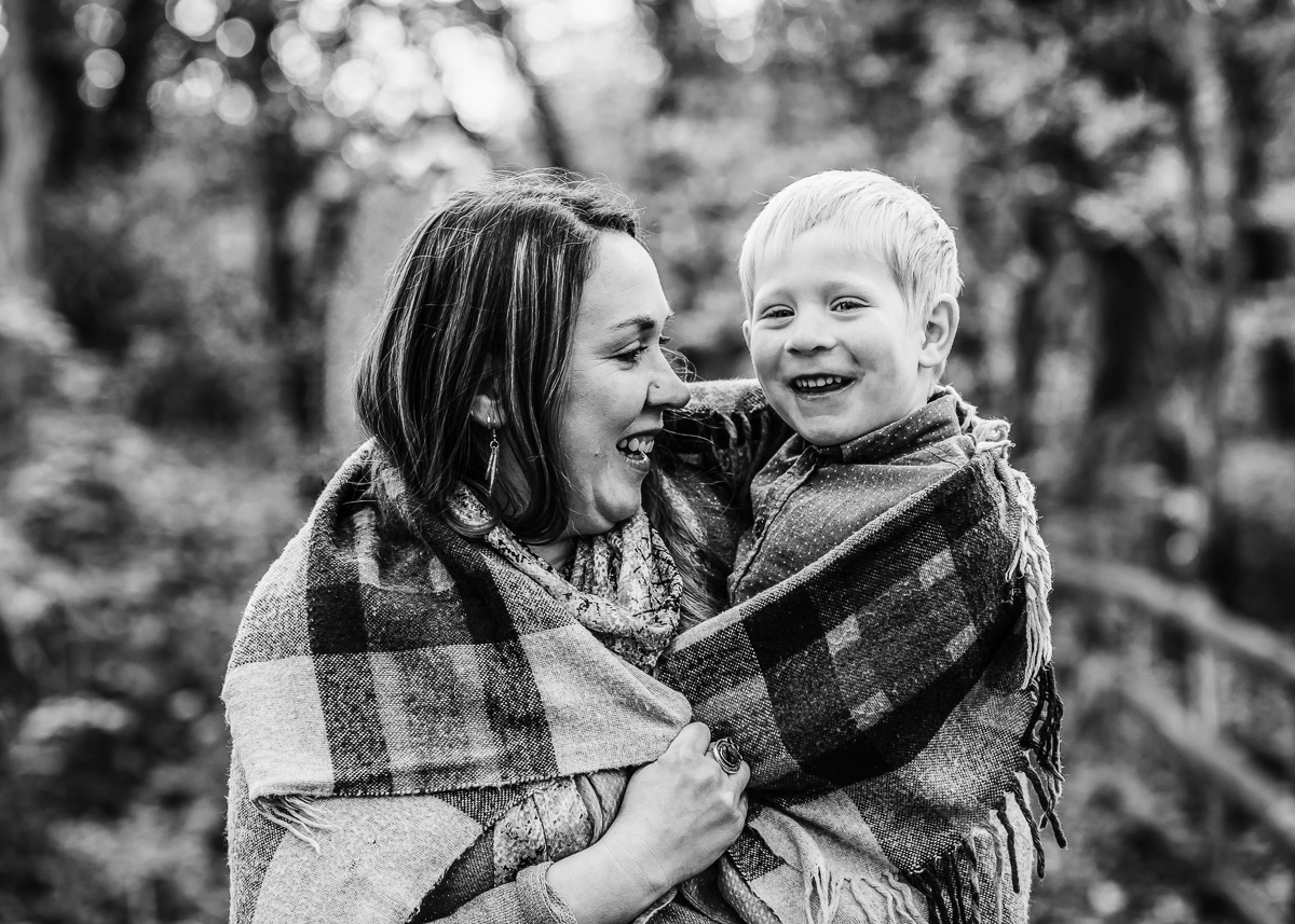 Copy of Mum and son cuddle under a blanket in the forest.
