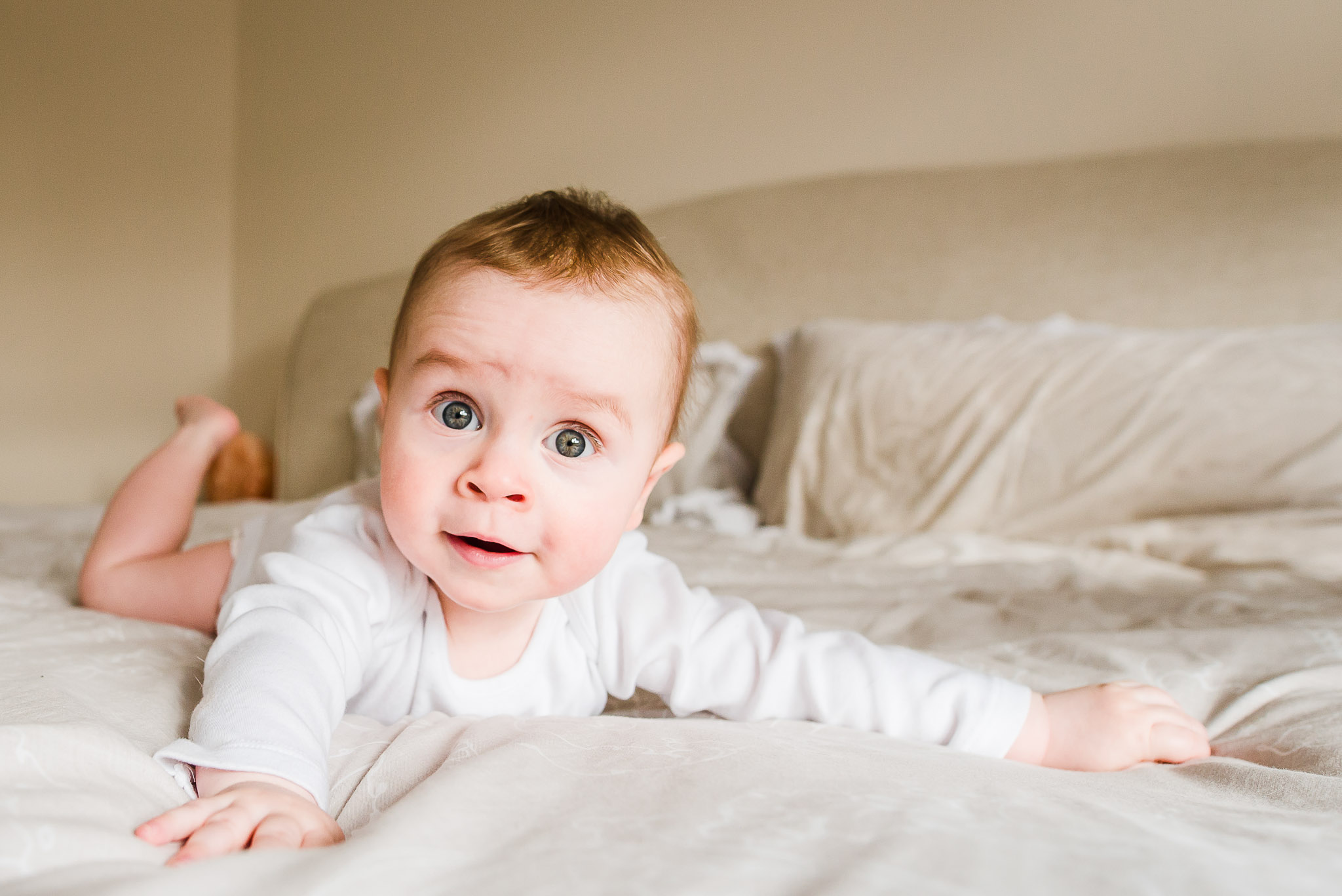 Copy of Baby boy posing on parent's bed - adorable smile. Baby portrait.