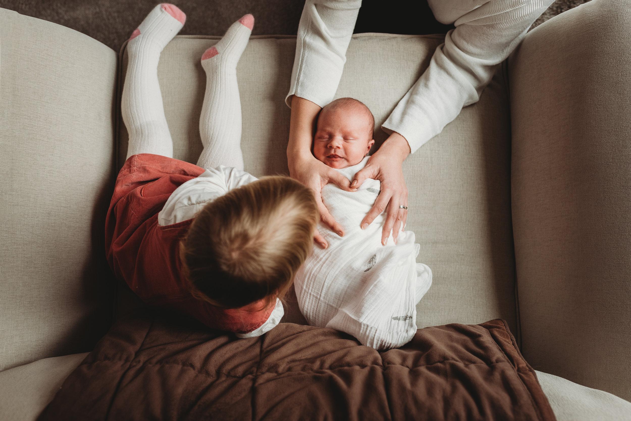Sibling photo. Bug sister comforts newborn baby sister.