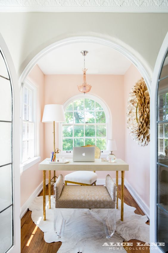 all in the details - the light pink walls, touches of gold, and large windows make this small space feel so large and inviting while also sparking creativity and dedication.