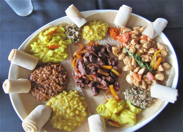 A feast of meat and vegetable tibs and wots served atop injera bread with rolls of injera for grabbing morsels of food.