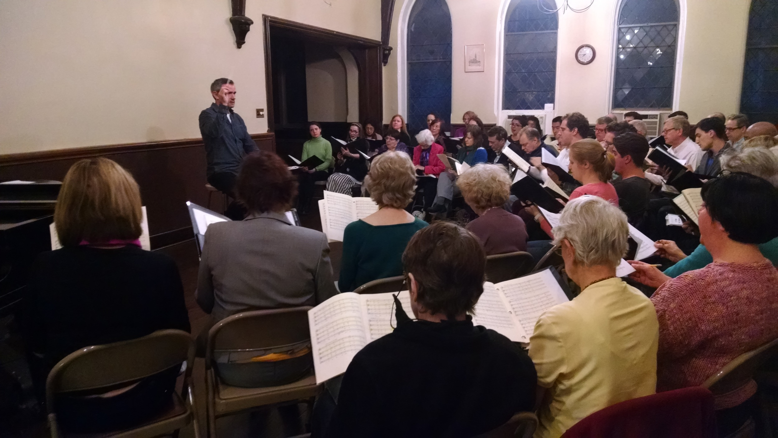 "Artistic Director Matthew Lewis leading the choir at its April 13, 2016 rehearsal for ""Sacré et Profane - Choral Music from Paris."""