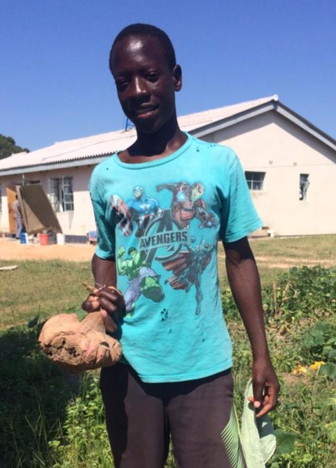 Tendai shows off a giant sweet potato he has carefully cultivated in his family garden