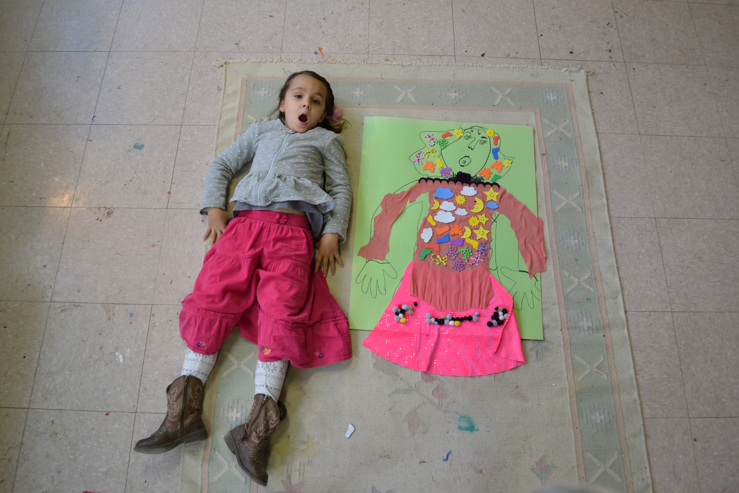 Aoloni mimics her self portrait on the floor