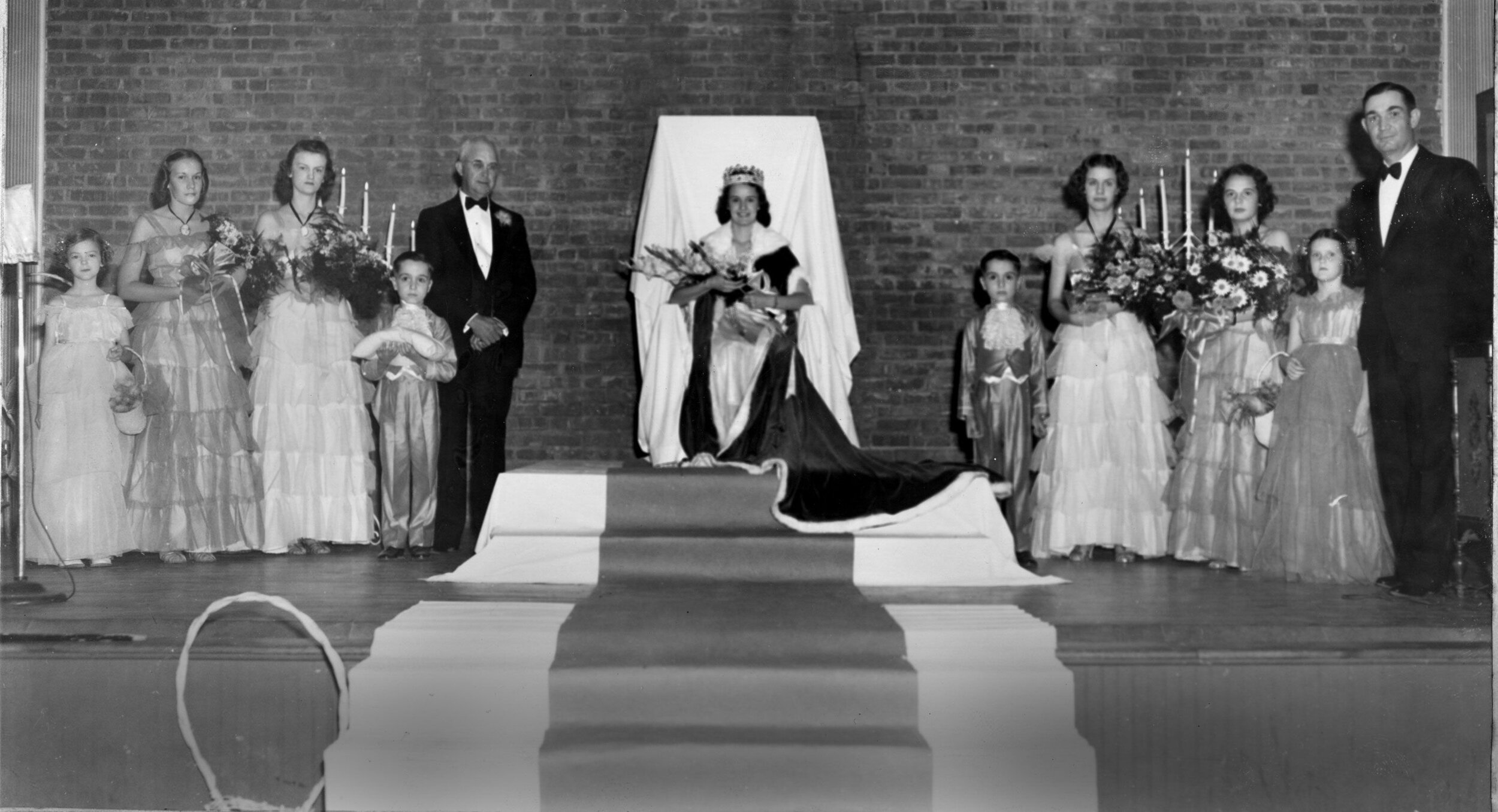 First Mimosa Festival – June 23, 1938. Left to right: Sarah Lou Davis, flower girl; Nancy Harbison and Ann Huffman, attendants; John Wilson, crown bearer; Benedict Bristol, Mayor of Morganton who crowned the Queen; Margaret Chaffee, the first Mimosa Queen; David Wilson, page; Elizabeth Sharpe Erwin and Betty Gaither, attendants; Martha Fuller Chaffee, (sister of the Queen) flower girl; Frank C. Patton, master of ceremonies. Photo contributed by the Burke Co. Pub. Library