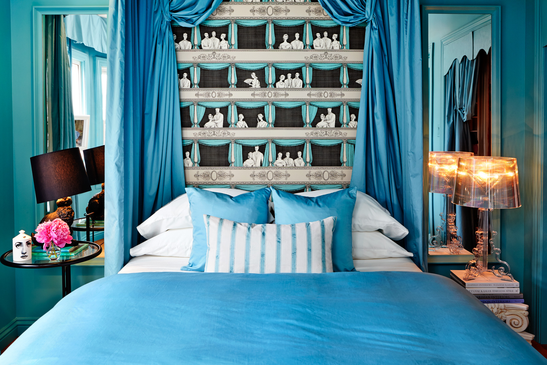 "The ""Bleu"" room draws its inspiration from Marie Antoinette. The canopy bed is paired with fantastical wallpaper by Fornasetti, referencing Marie Antoinette's theatre at Versailles. Custom designed canopy bed, fabric Ikea; ""Il Teatro"" Wallpaper, Fornasetti by Cole and Son; Rabbit Lamp, Moooi; Bourgie Lamp, Ferruccio Laviani for Kartell; Striped pillow custom, fabric Brunschwig & Fils."