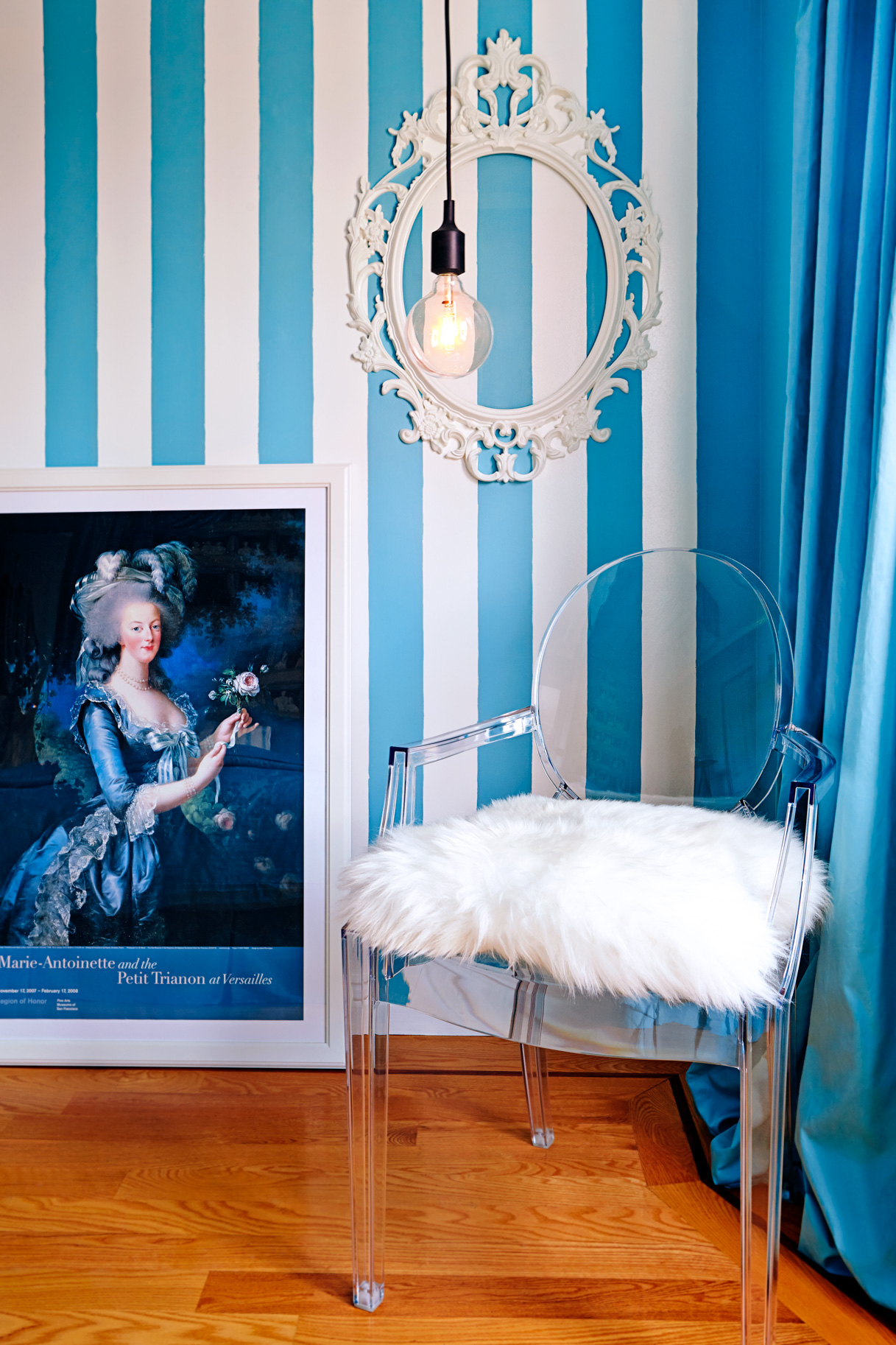A Phillippe Starck Louis Ghost sits comfortably with classic stripes, an empty Rococo frame, a Muuto hanging lamp, and Marie Antoinette leans in.