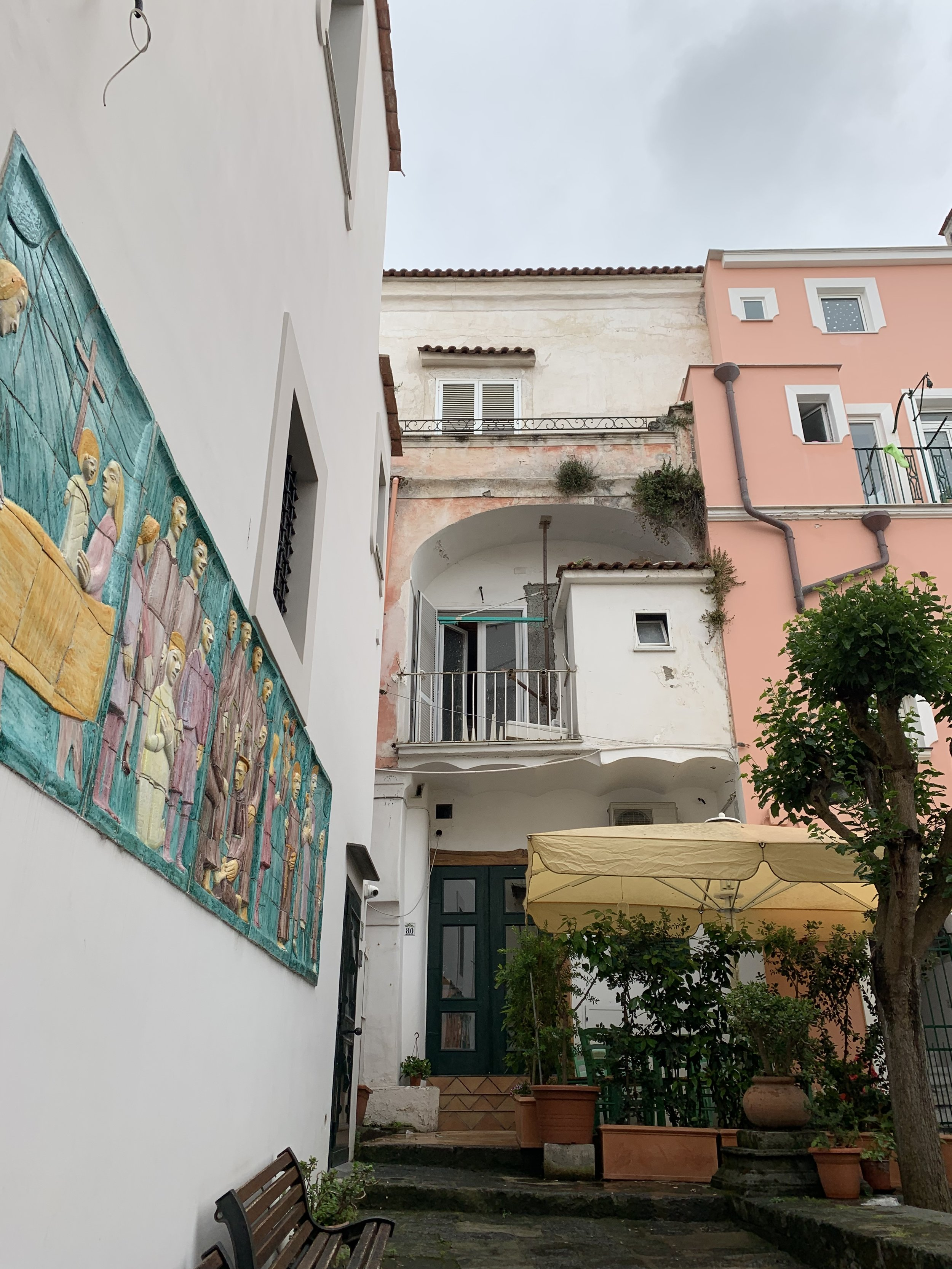 Pink and white buildings in town | EAT.PRAY.MOVE Yoga Retreats | Ischia, Italy