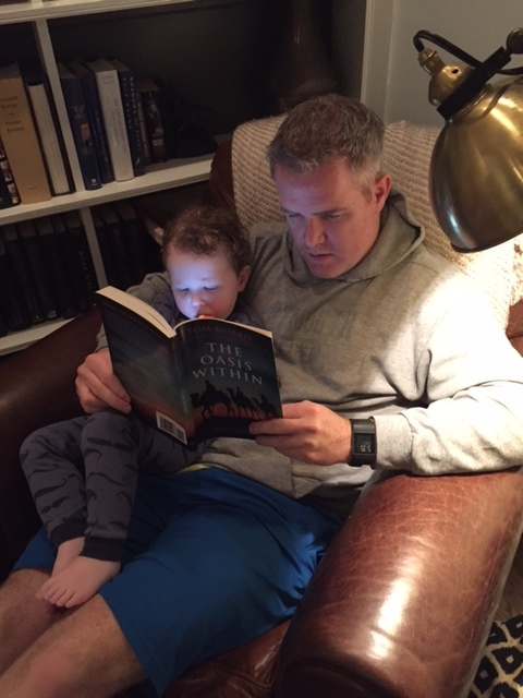 A busy business executive reads The Oasis Within, along with his small son, February 2016.