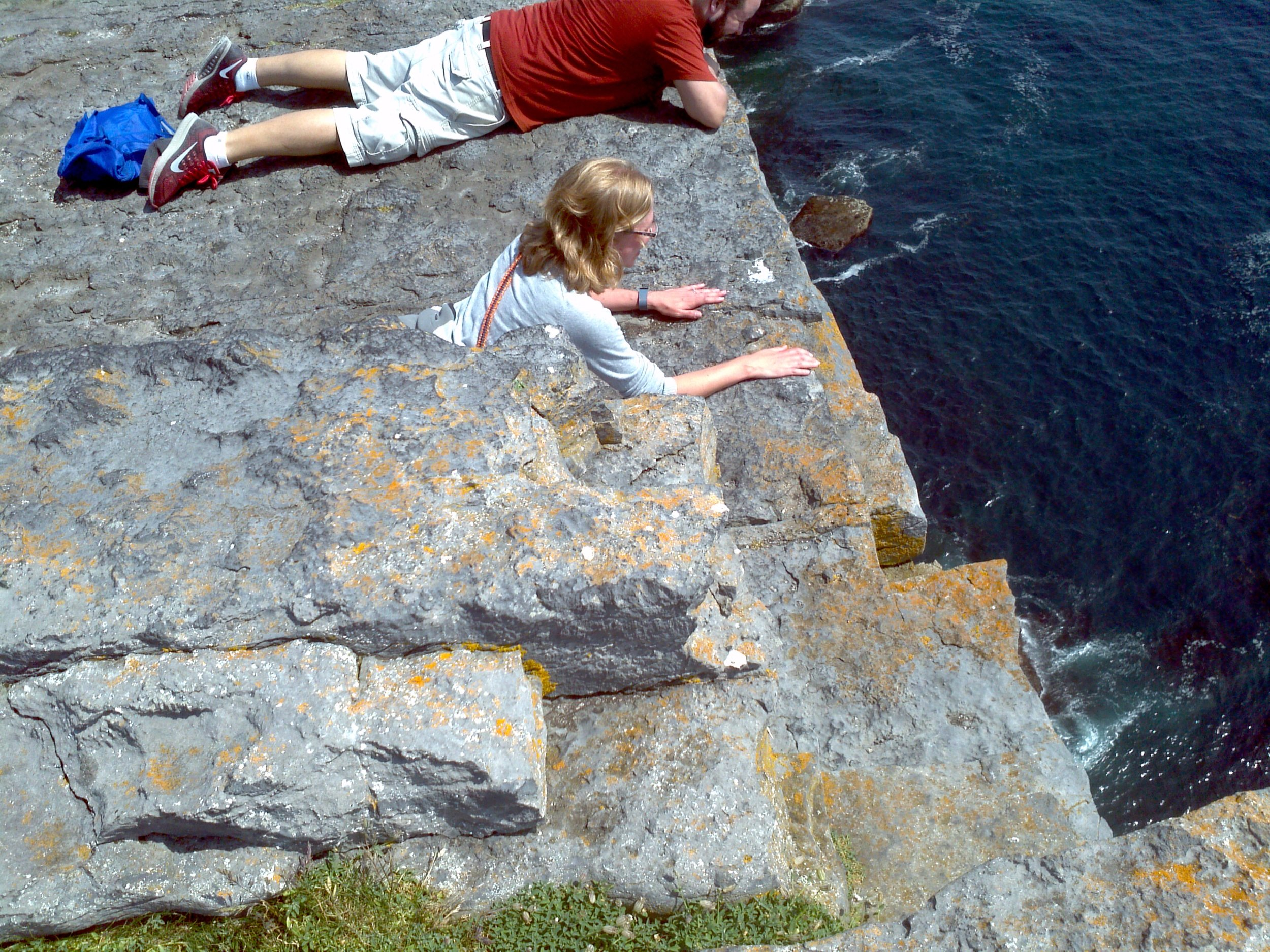 Megan belly crawls to the edge of the three-hundred-foot cliff.