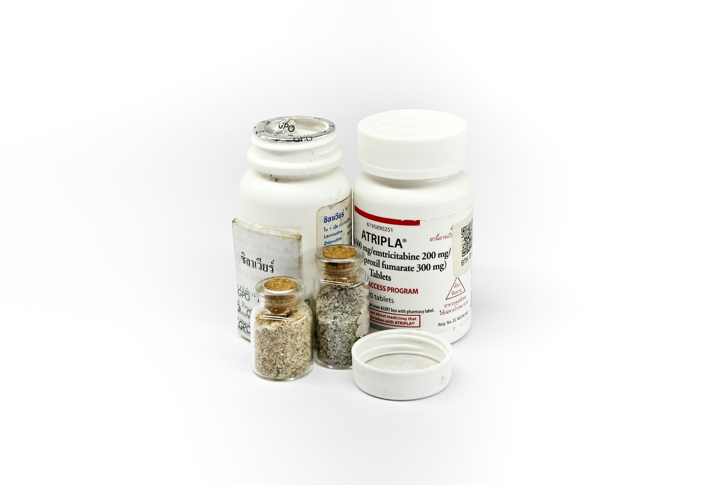 HIV medication bottle and sand