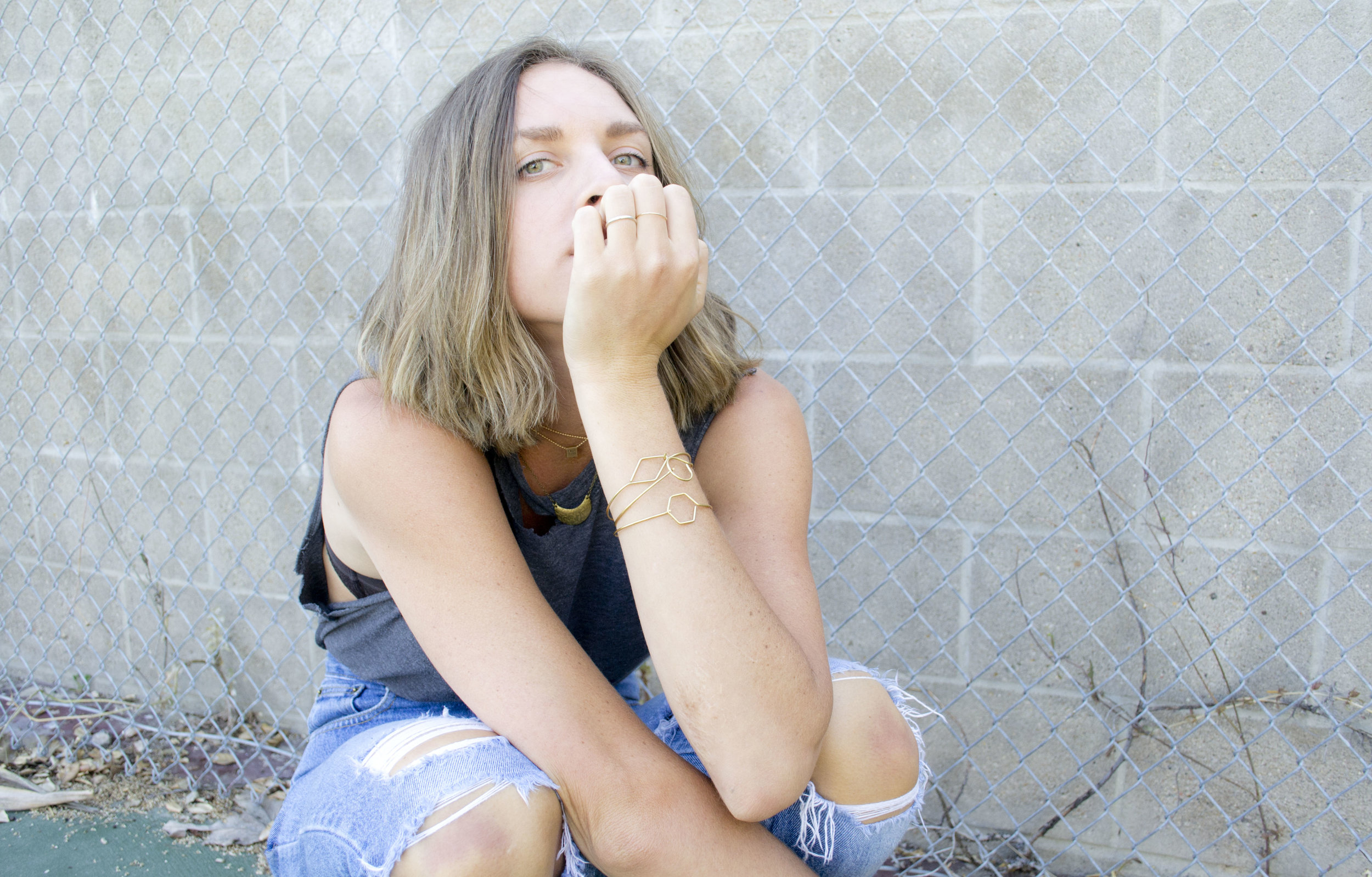 Model is crouched in a tennis court with her hand under her chin. She is wearing Grey Theory Mill wire cuffs on her wrist, ball chain chokers on her neck, and a patterned moon necklace for layering
