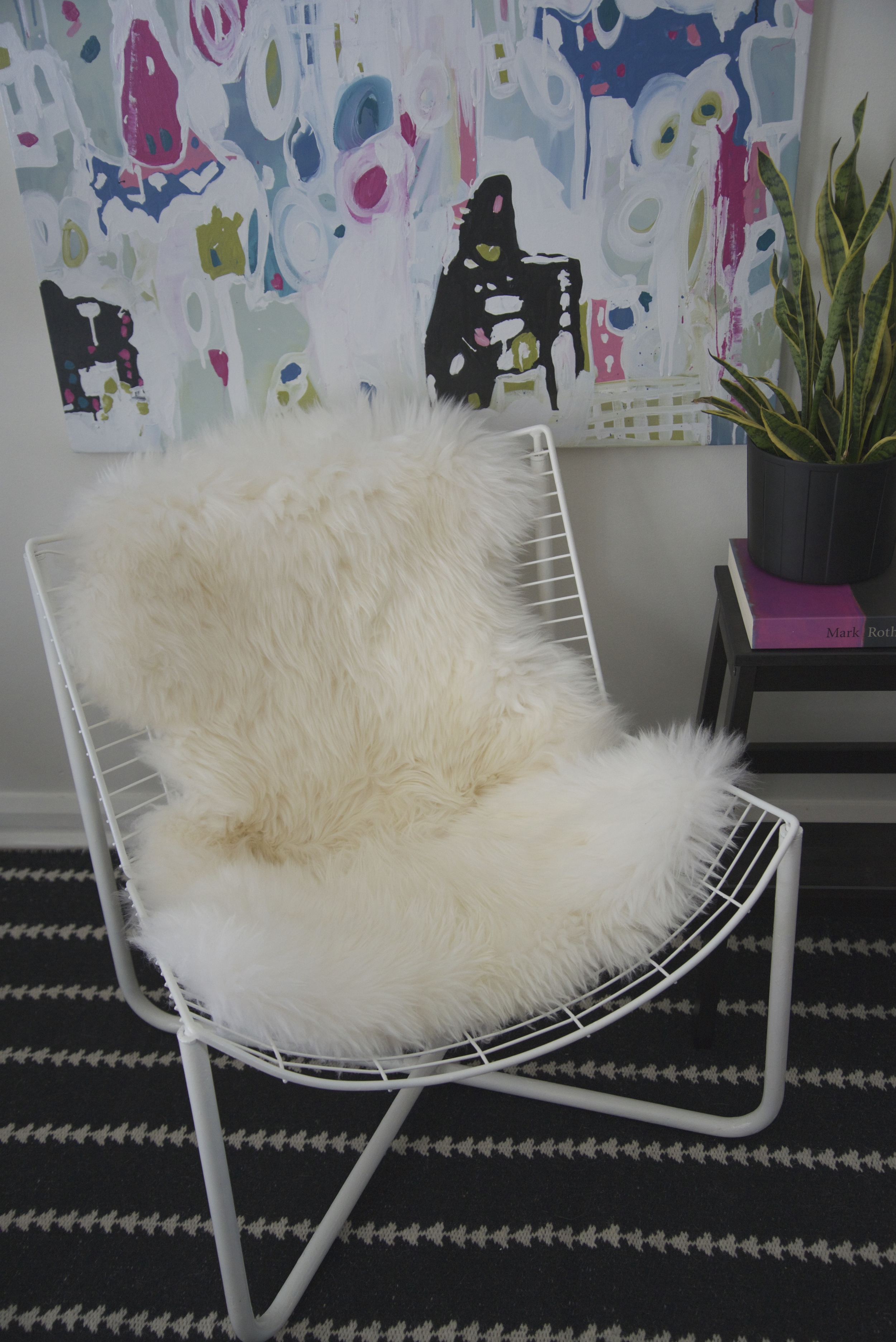 This chair reminds me of a Bertoia style, the sheepskin softens up the look.