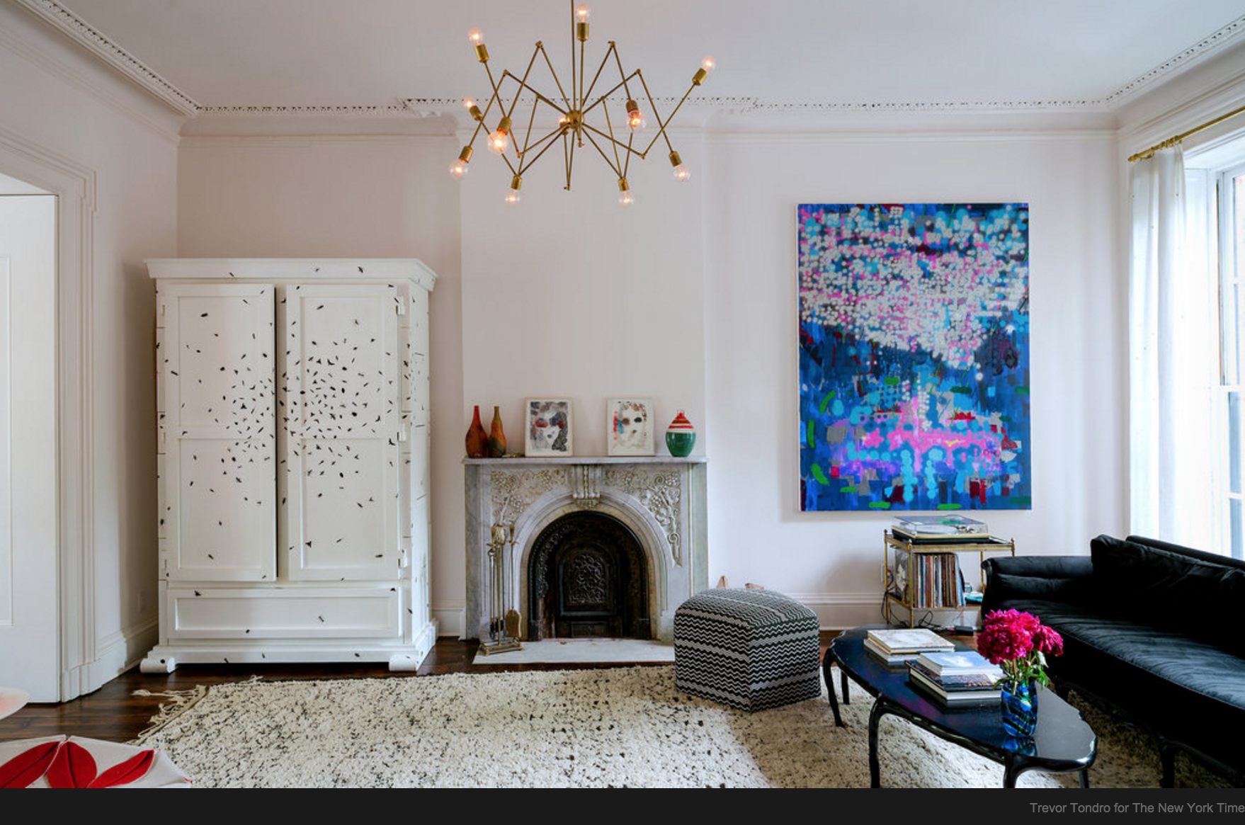 You do not have to hang a large piece of art or a mirror over a mantle.The armoire and painting are both rectangular, the symmetry and placement of them on either side of the fireplace make this wall balanced.