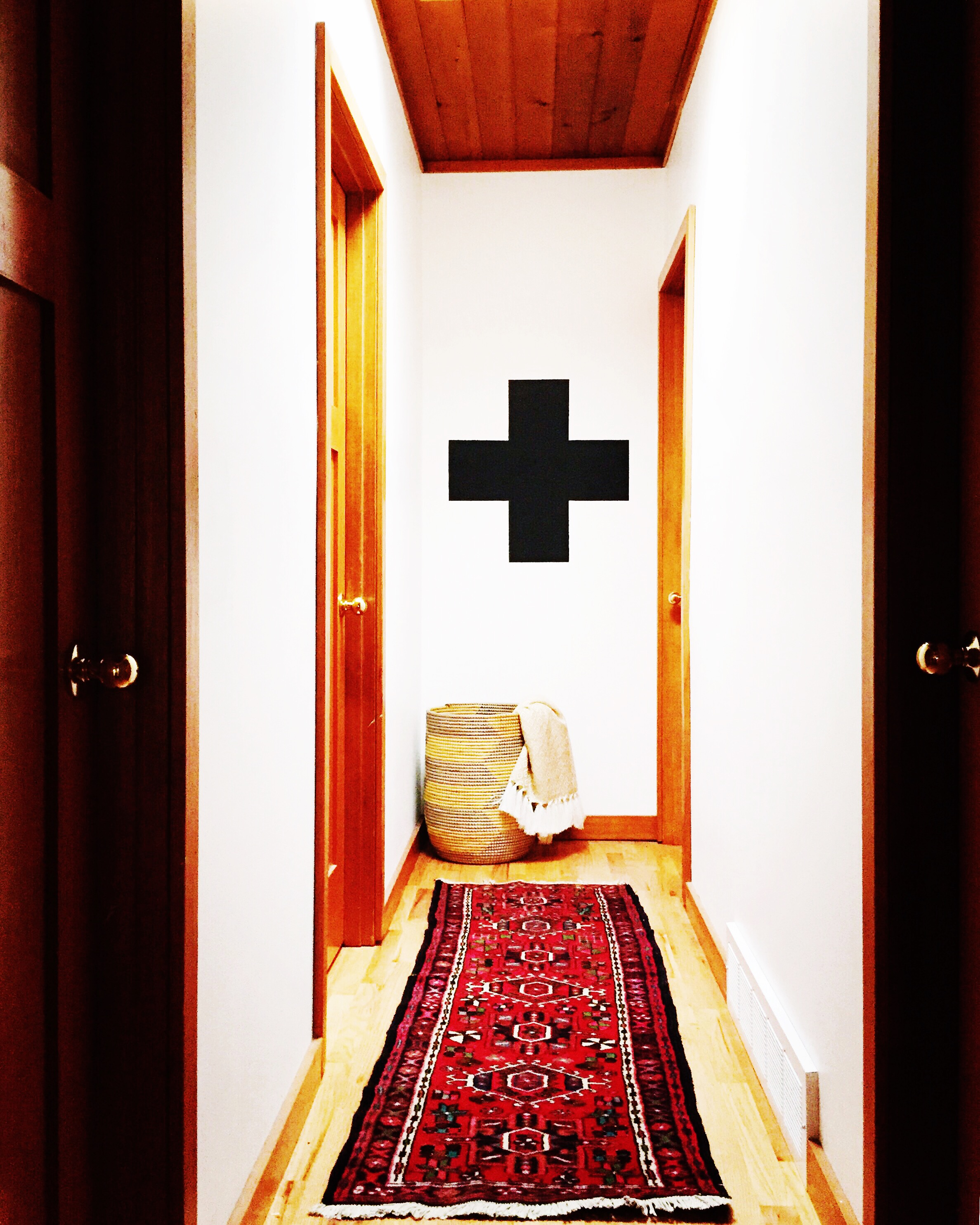 This hallway leads you to the bedrooms. Audrey recently painted this cross on the wall & wasn't sure if her husband would like it. He came home from work & helped her measure to make sure it was perfect. True DIY love people!