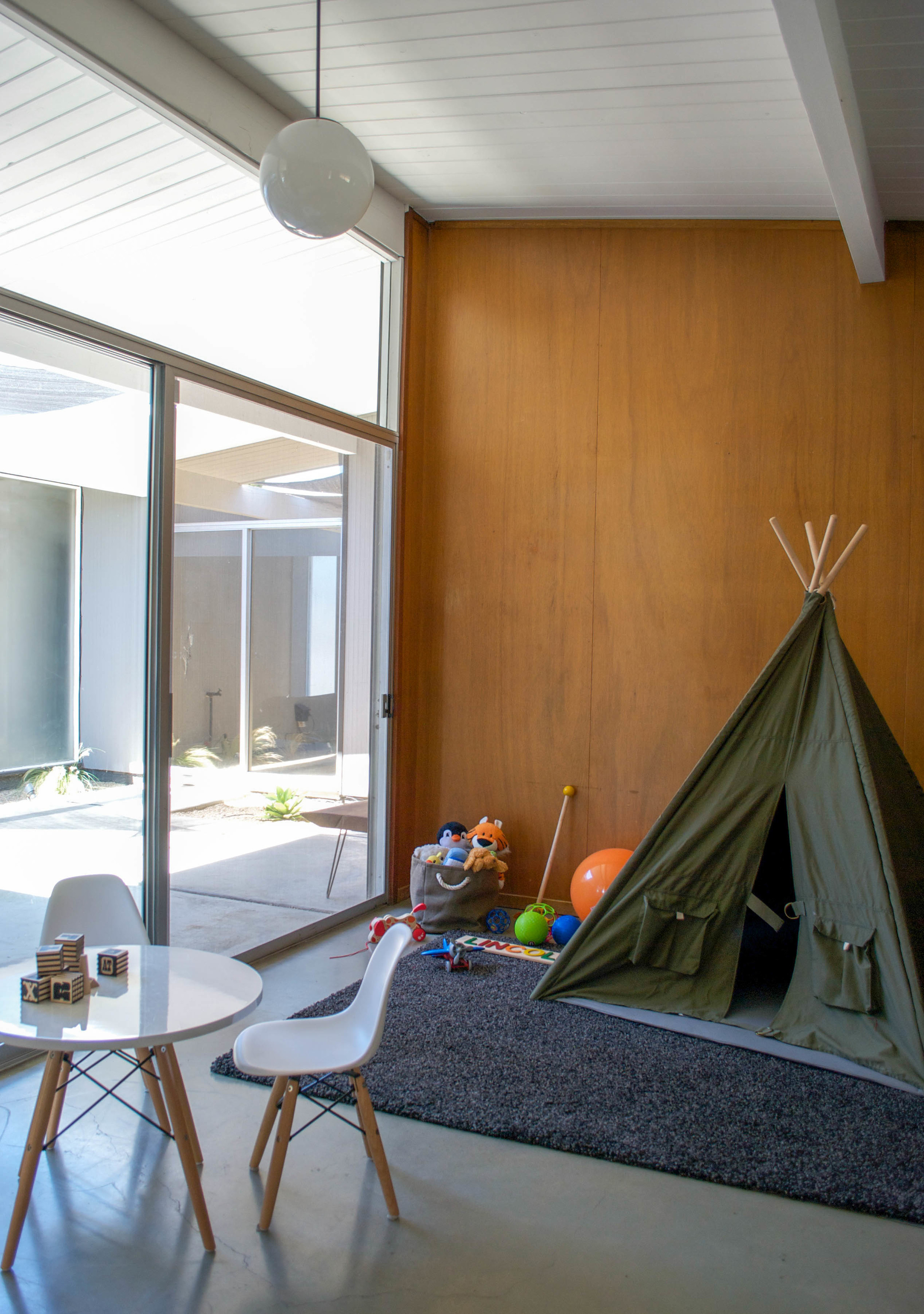Lincoln's playroom is furnished with a modern table and chair set,as well as a spot to camp out and get cozy.